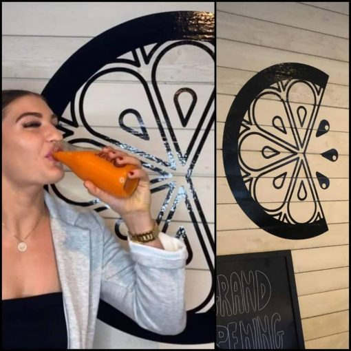 Large Orange Slice on wall with a woman drinking juice