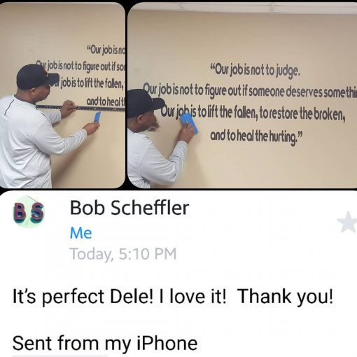 Dele installing wall graphics in an office building board room.