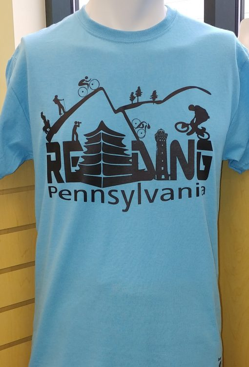 The reading bike and hike t-shirt has waves of trails over the letters READING Pennsylvania. There is a person with binoculars, a man walking a dog and hikers and bike riders.